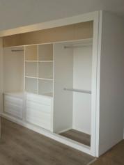 Interior de armario forrado en melamina blanca, con cajoneras y baldas