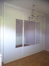 Frente de armario de puertas correderas a medida, en blanco con espejo central