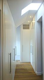 Armario vestidor a medida, de diseño moderno y sencillo, en blanco, con puertas abatibles
