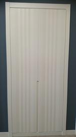 Armario a medida lacado blanco, de puertas abatibles, tirador fresado y embutido, diseño moderno