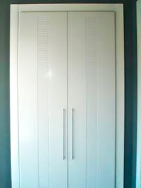 Armario a medida lacado blanco, de puertas abatibles, tirador de barra, diseño moderno fresado