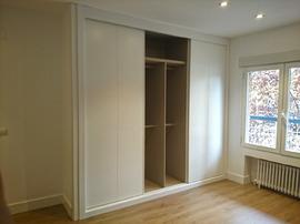 Armario empotrado blanco de puertas correderas, con el interior en melamina textil.