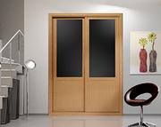 Frente de armario a medida de puertas correderas, perfilería four roble barniz, puerta roble barnizado/cristal negro con decoracion moldura roble barniz.