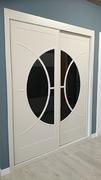 Frente de armario a medida de puertas correderas, perfilería fine blanco, puerta lacada fresada blanca de diseño vanguardista/cristal chocolate circulo.