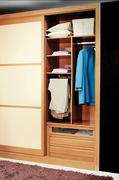 Interior de armario empotrado a medida con baldas, pantalonero, perchero y cajonera con cristal