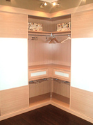Interior de armario empotrado en esquina, combinando melamina en haya y cristal lacado blanco