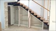 Armario abohardillado bajo escalera de 6 puertas abatibles en melamina textura y tiradores en acero inoxidable.