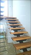 Escalera con barandilla en acero y cristal laminado, con los peldaños en haya vaporizada.