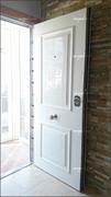 Puerta acorazada vista por la cara exterior con plafón en aluminio lacado blanco.