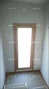 Puerta exterior balconera con la cara exterior en aluminio lacado blanco e interior en madera tecnológica.