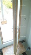 Detalle de la cerradura de puerta exterior balconera, con la cara exterior en aluminio lacado blanco e interior en madera tecnológica.